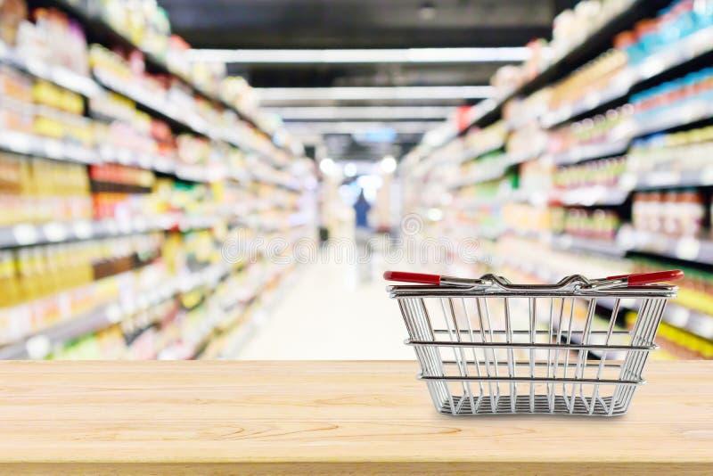 Lege het Winkelen mand op houten lijst over kruidenierswinkelopslag stock afbeelding
