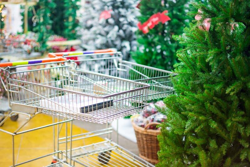 Lege het winkelen manden in de winkel, Kerstmismarkt met groene Kerstbomen voor verkoop op de achtergrond Prepearing voor Christm royalty-vrije stock foto's