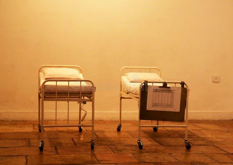 Lege het ziekenhuisbedden die zich in verlaten ruimte voor patiënten bevinden stock foto