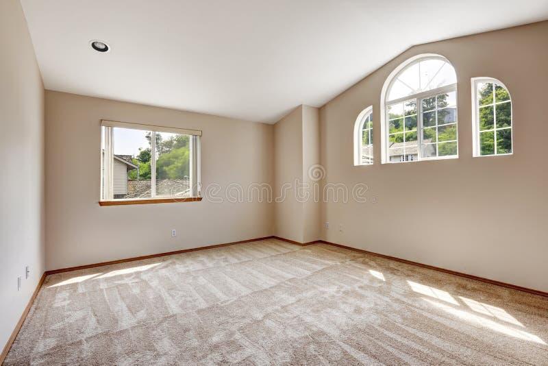 Lege hoofdslaapkamer met venster en hoog gewelfd plafond stock afbeelding
