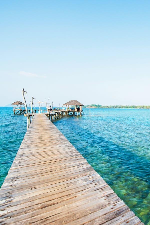 Lege houten brug die zich in het duidelijke blauwe overzees, de heldere de zomerochtend, de mooie wolken en de lichtblauwe hemel  royalty-vrije stock afbeelding