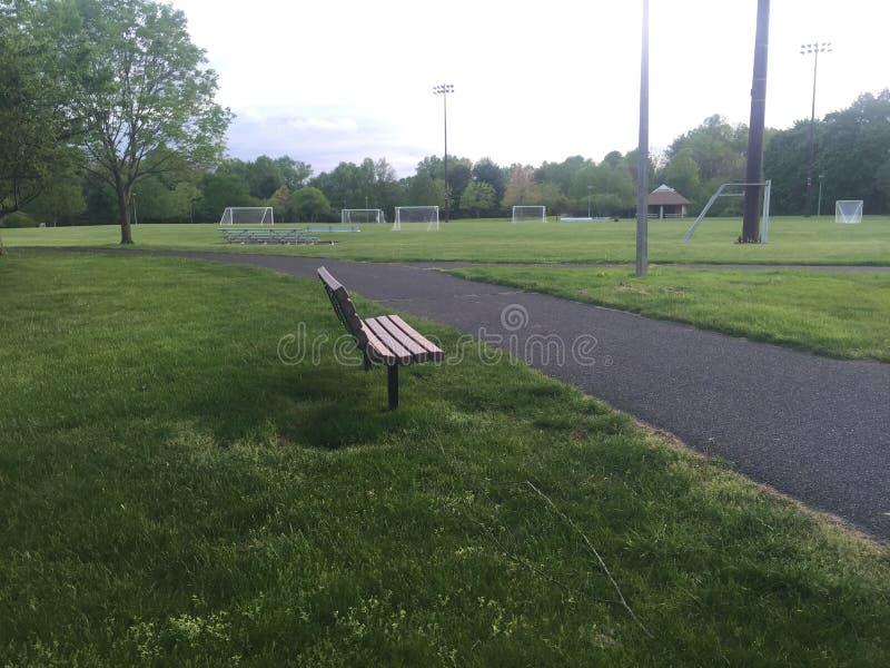 Lege houten die parkbank door groene gras en asfaltsleep wordt omringd Sportterreinen in afstand stock afbeelding