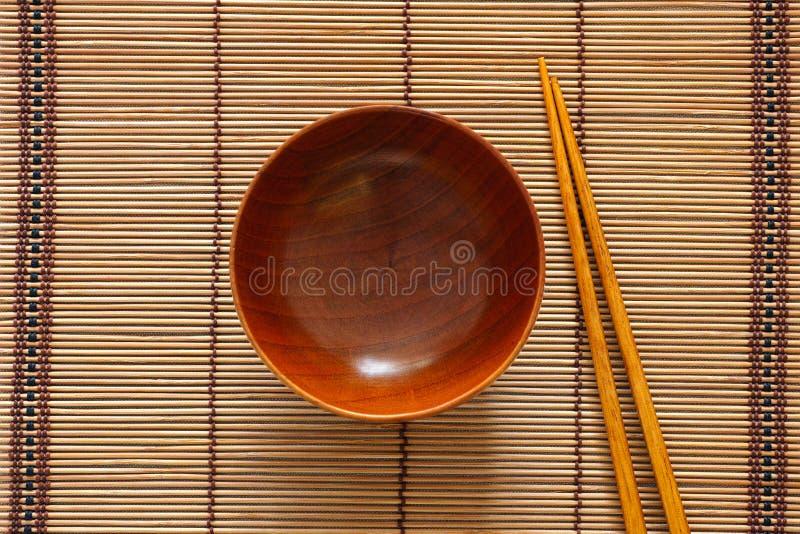 Lege houten kom en eetstokjes stock afbeelding