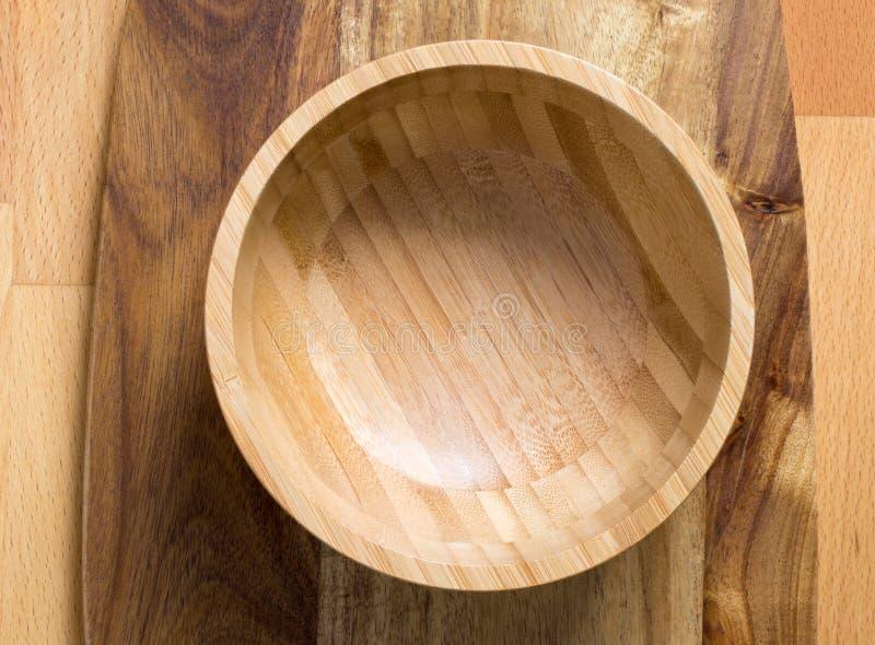 Lege houten kom op houten scherpe raad op houten achtergrond stock fotografie