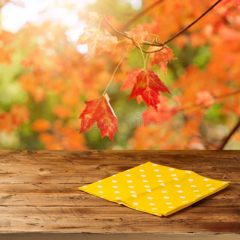 Lege houten lijst met tafelkleed over de achtergrond van dalingsbladeren Het seizoen van de herfst Weg in dalingsbos royalty-vrije stock foto's