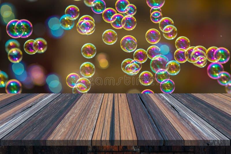 Lege houten lijst of plank met bokeh van regenboogzeepbels van de bellenventilator op achtergrond voor productvertoning royalty-vrije stock foto