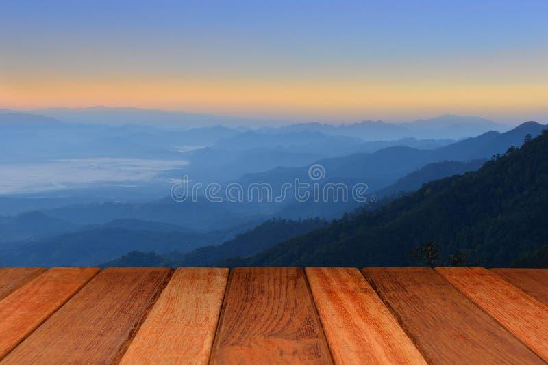 Lege houten lijstbovenkant met bergachtergrond bij zonsopgang stock foto's