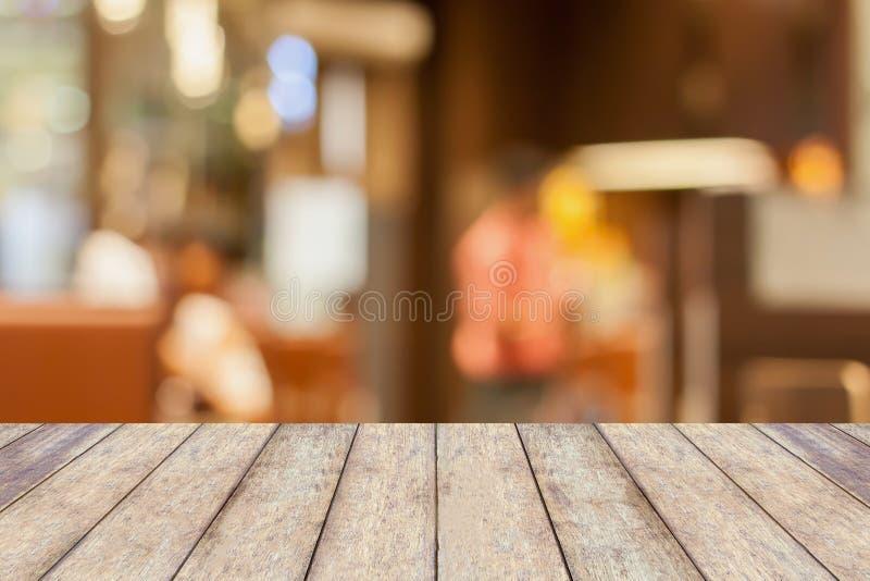 Lege houten lijstbovenkant met restaurantonduidelijk beeld met bokehachtergrond stock foto