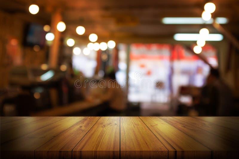 Lege houten lijstbovenkant met vage koffiewinkel of restaurant binnenlandse achtergrond De abstracte achtergrond kan voor vertoni stock foto's