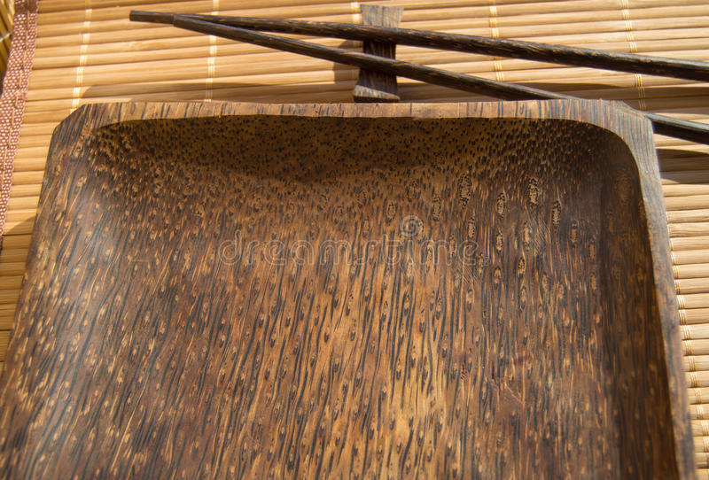 Lege houten plaat en sushieetstokjes op bamboeservet royalty-vrije stock foto