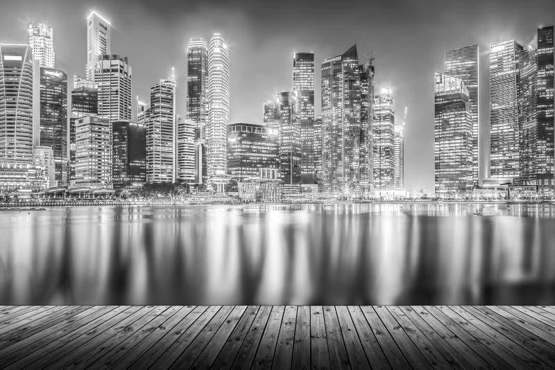 Lege houten plank met de moderne cityscape bouw bij nacht in mono stock foto
