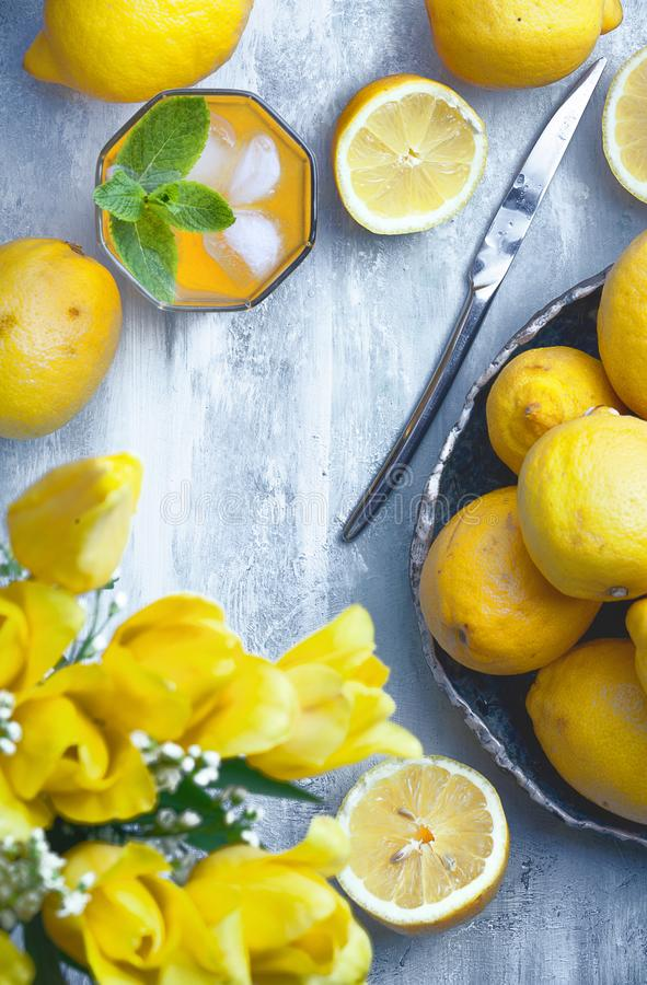 Lege houten raad met gele bloemen, citroenen, glas sap en mes, met exemplaarruimte stock foto's