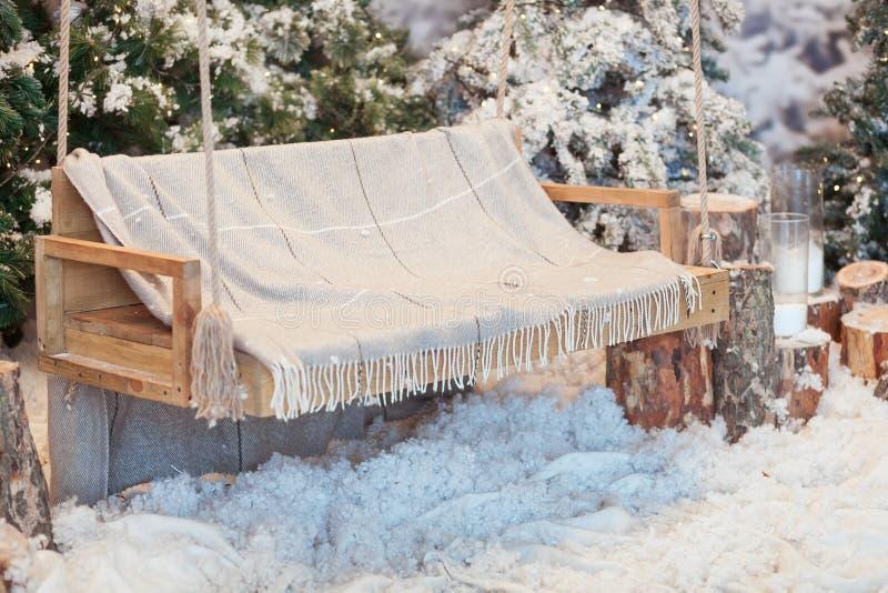 Lege houten schommeling in een snow-covered park of een bos met nette bomen en stompen, grote kaarsen in glasvazen, terwijl stock foto's