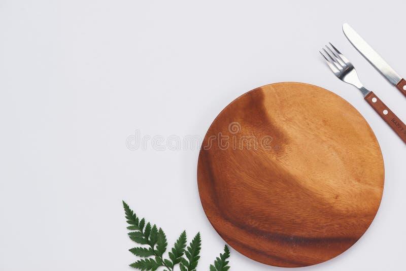 Lege houten schotel met mes en vork op witte achtergrond, Bovenkant v stock foto