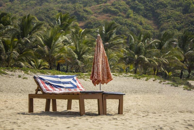 Lege houten strandlanterfanters met matrassen en een gevouwen zonparaplu op het witte zand tegen de achtergrond van de groene pal stock afbeeldingen