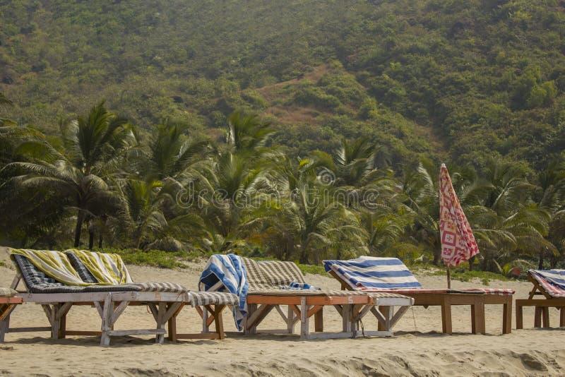 Lege houten strandlanterfanters met matrassen op het zand tegen de achtergrond van de groene palmwildernis op de heuvel royalty-vrije stock foto's