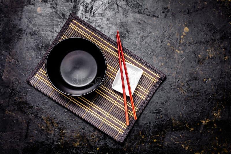 Lege Japanse schotels Een zwarte ceramische kom voor Chinese noedels of Thaise soep ligt op een bamkukdeken Witte saucepot voor s stock afbeelding