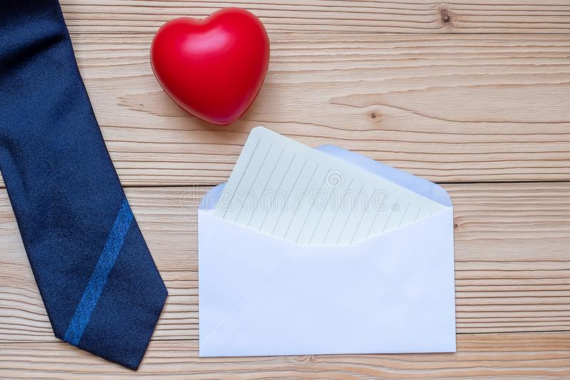 Lege kaart met blauwe stropdas en rode hartvorm op houten achtergrond met exemplaarruimte voor tekst Gelukkige Vaderdag en stock foto's