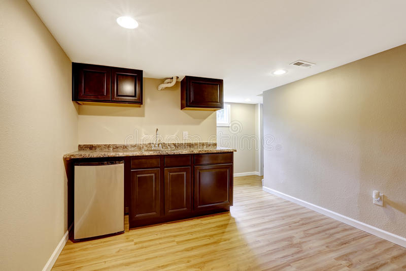 Lege kelderverdiepingsruimte met donkere bruine keukenkasten royalty-vrije stock afbeeldingen