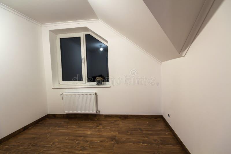 Lege kleine ruimte met houten eiken parketvloer, onlangs geschilderde witte muren, het verwarmen radiator en een venster Zolder r stock fotografie