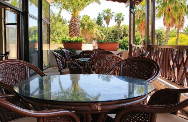 Lege lijsten en stoelen in een koffie op een gesloten terras in een hotel royalty-vrije stock afbeelding
