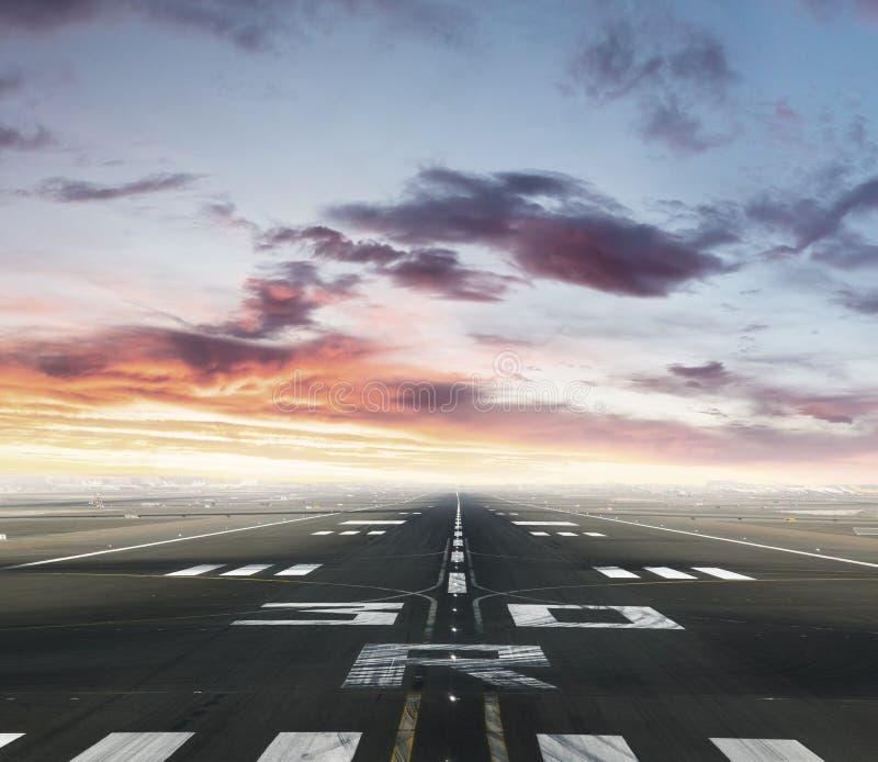 Lege luchthavenbaan in zonsondergang stock foto