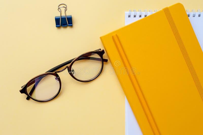 Lege notitieboekje en bureaukantoorbehoeften gele achtergrond stock fotografie