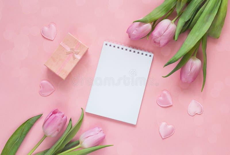 Lege open blocnote met tulpen, giftdoos en harten op roze bedelaars stock foto's