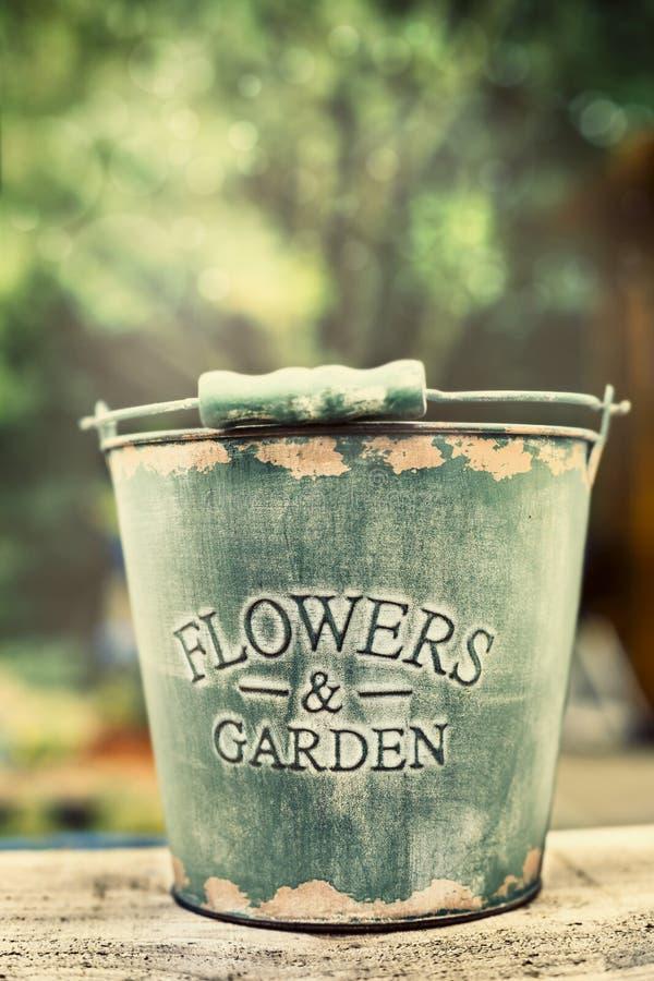 Lege oude emmer op tuinlijst, het tuinieren concept stock afbeelding