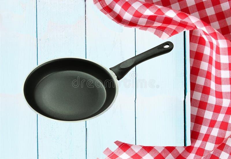 Lege pan en een rood wit geruit tafelkleed op een houten brigh royalty-vrije stock foto's
