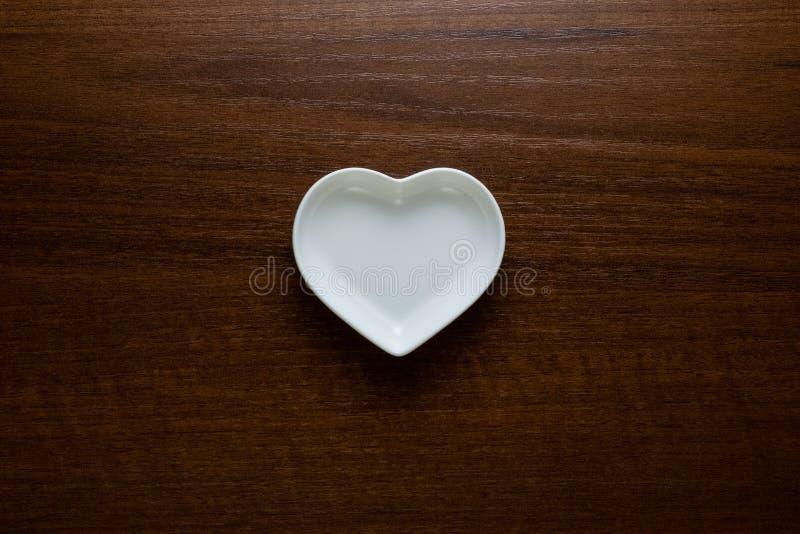 Lege plaat in de vorm van een hart op een houten lijst in het centrum van het kader Ceramische glanzende schotels op een donkere  stock afbeelding