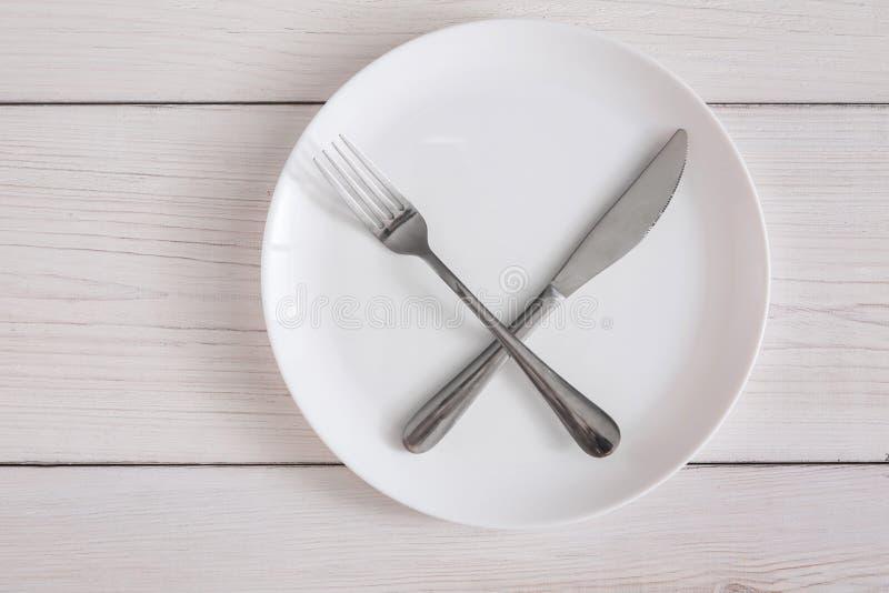 Lege plaat met gekruiste vork en mes op witte houten hoogste mening royalty-vrije stock foto's