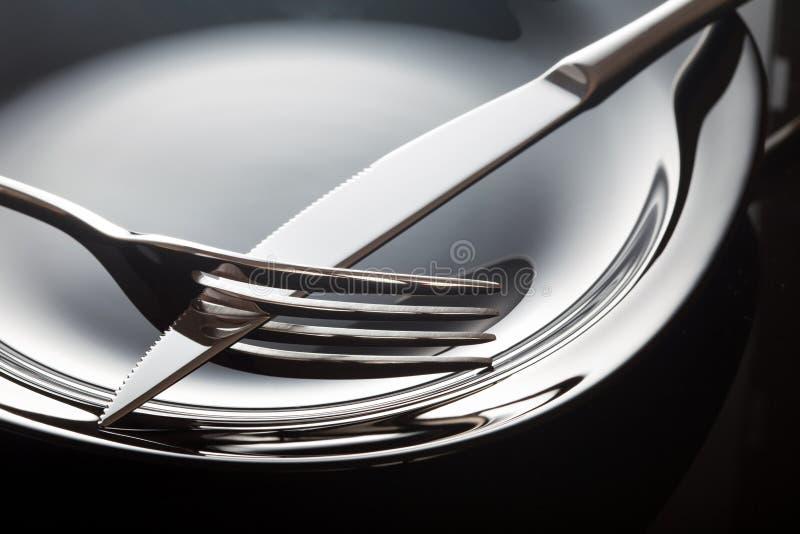 Lege plaat met lepel, mes en vork op een zwarte achtergrond stock afbeeldingen