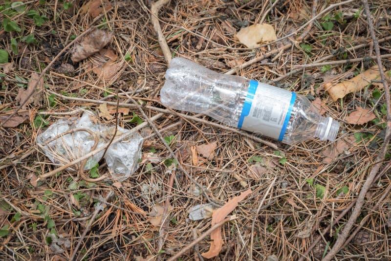 Lege plastic fles die rond in het Park op de grond liggen stock afbeelding