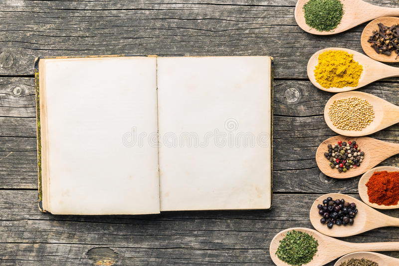 Lege receptenboek en kruiden in houten lepels stock afbeelding