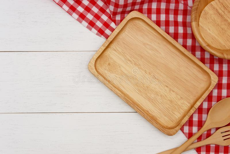 Lege rechthoek houten plaat met lepel, vork en rood gingangtafelkleed op witte houten lijst royalty-vrije stock fotografie