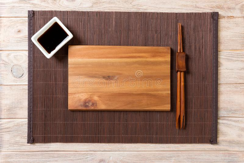 Lege rechthoekige houten plaat met eetstokjes voor sushi en sojasaus op houten achtergrond Hoogste mening met exemplaarruimte stock afbeelding