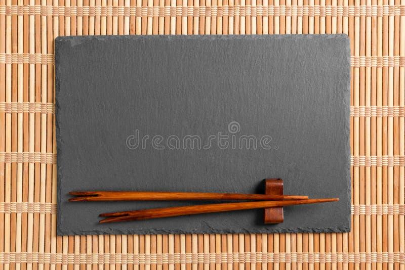 Lege rechthoekige zwarte leiplaat met eetstokjes voor sushi op houten achtergrond Hoogste mening met exemplaarruimte stock foto
