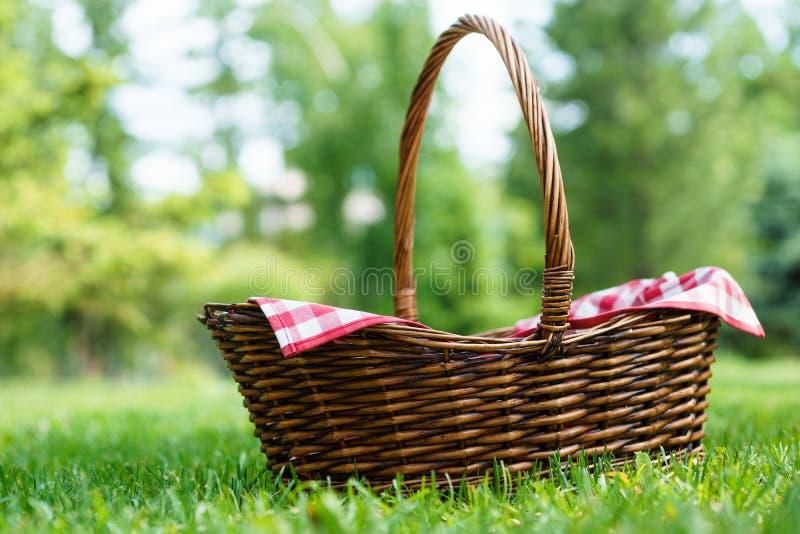Lege rieten mand met rood tafelkleed op groen gras in een park royalty-vrije stock afbeelding