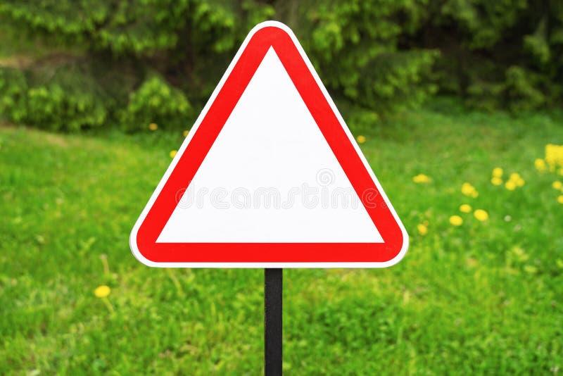 Lege rode driehoeksverkeersteken met niet tekst en teken op de straat en groene bomen op de achtergrond royalty-vrije stock foto