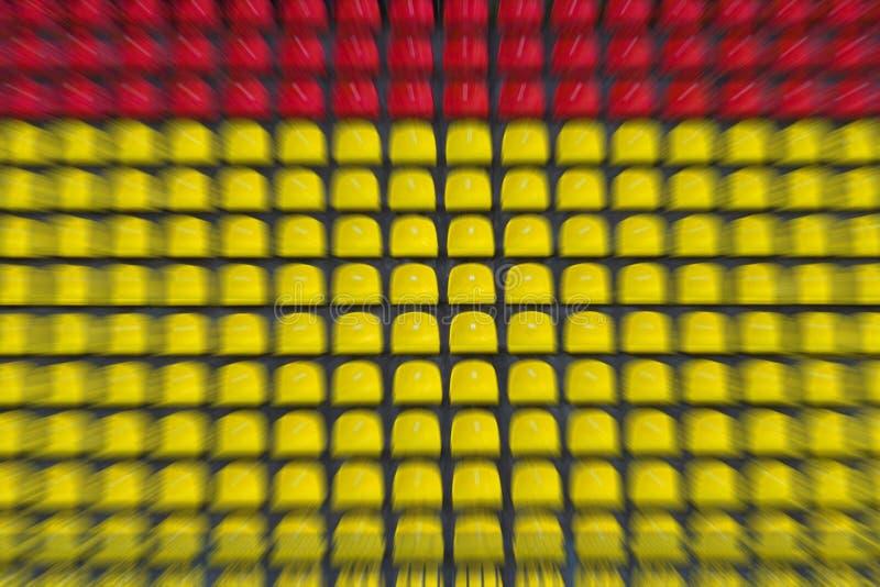 Lege rode en gele plastic stoelen op een rij bij voetbalsta stock afbeeldingen
