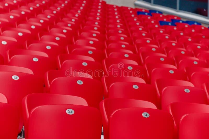Lege rode plastic stoelen op een rij bij het voetbalstadion stock afbeelding