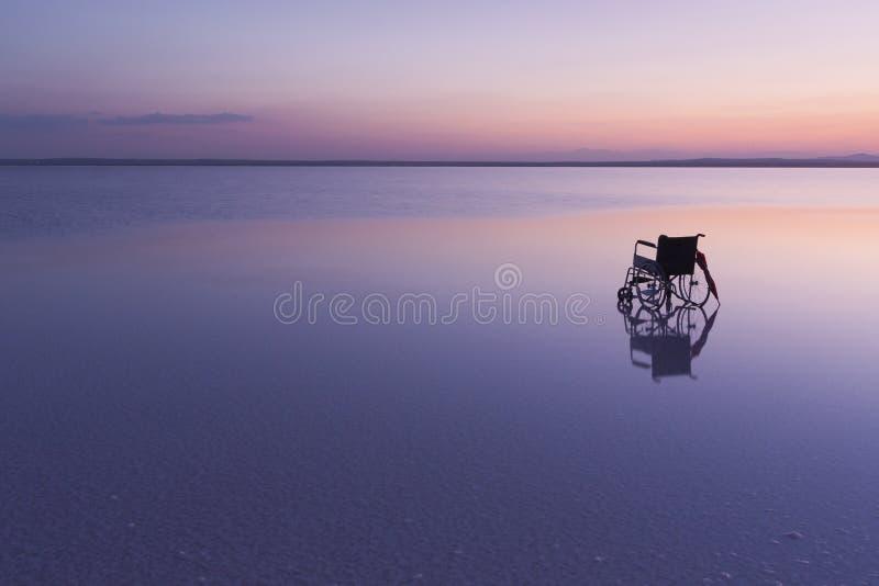 Lege rolstoel op het meer bij zonsondergang met mooie kleuren royalty-vrije stock afbeelding