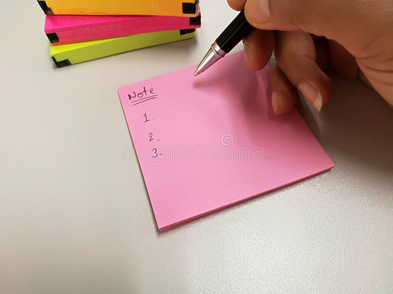 Lege roze document nota gezet dichtbij pen en pak van kleurrijke papernote royalty-vrije stock afbeelding