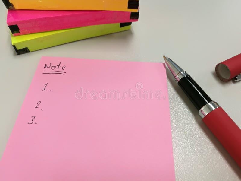 Lege roze document nota gezet dichtbij pen en pak van kleurrijke papernote stock foto
