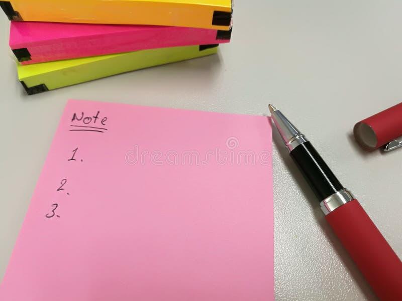 Lege roze document nota gezet dichtbij pen en pak van kleurrijke papernote royalty-vrije stock foto's
