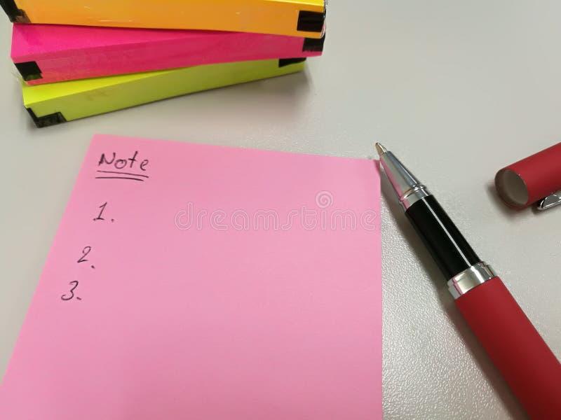 Lege roze document nota gezet dichtbij pen en pak van kleurrijke papernote stock afbeelding
