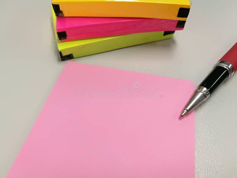 Lege roze document nota gezet dichtbij pen en pak van kleurrijke papernote stock afbeeldingen