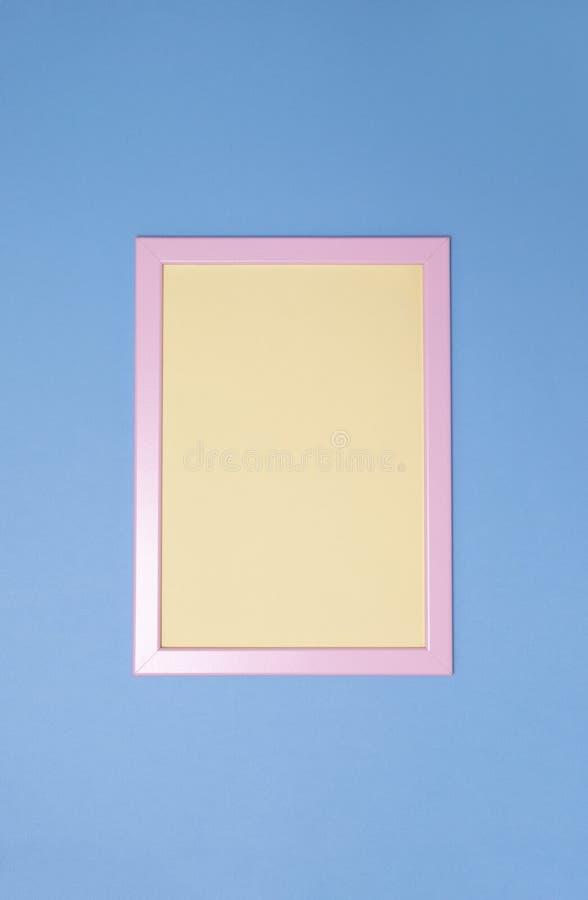 Lege roze photoframe met geel document binnen op blauwe achtergrond De ruimte van het exemplaar Hoogste mening verticaal royalty-vrije stock foto's