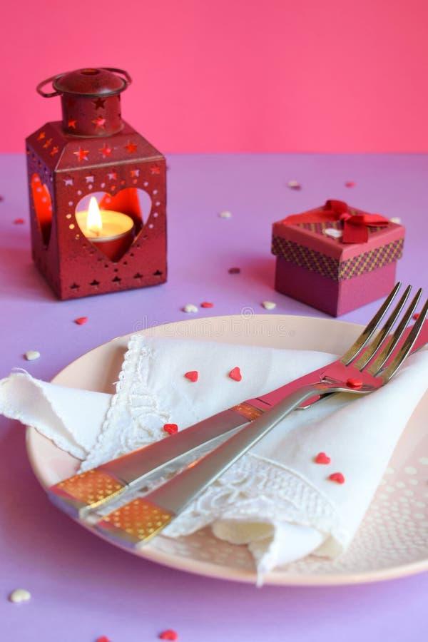 Lege roze plaat, bestek, harten, kandelaars en rode gift op roze-purpere achtergrond St Valentine het plaatsende concept van de D royalty-vrije stock foto's